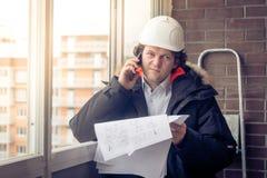 Stående av den bekymrade orakade byggmästaren som berättar vid mobilen, medan hålla olika projekt i hand Kommunikation och royaltyfria foton