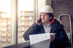Stående av den bekymrade orakade byggmästaren som berättar vid mobilen, medan hålla olika projekt i hand Kommunikation och royaltyfri fotografi
