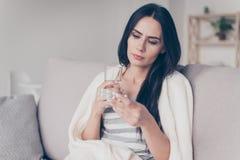 Stående av den besvärade dåligt unga kvinnan som sitter hemmastadd hållande gla royaltyfri fotografi