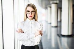 Stående av den blonda affärskvinnan med korsade händer i modernt kontor Arkivfoton