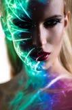 Stående av den blonda kvinnan med glänsande ljus på framsida royaltyfri foto