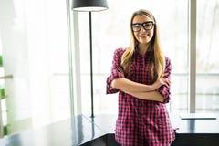 Stående av den blonda kvinnan med korsade händer i modernt kontor watch för penna för begreppsanteckningsbokkontor Royaltyfria Bilder