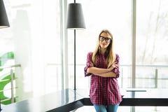 Stående av den blonda kvinnan med korsade händer i modernt kontor watch för penna för begreppsanteckningsbokkontor Royaltyfria Foton