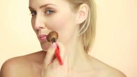 Stående av den blonda kvinnan som applicerar makeup lager videofilmer