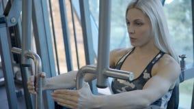 Stående av den blonda kvinnan som gör fjärilsövning i modrnidrottshall lager videofilmer