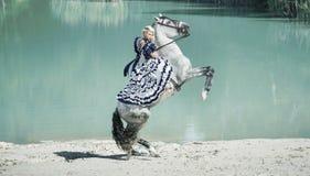 Stående av den blonda ridningen en häst Arkivbilder