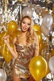 Stående av den blonda unga kvinnan mellan guld- ballonger och bandet Royaltyfri Bild