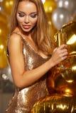 Stående av den blonda unga kvinnan mellan guld- ballonger och bandet Royaltyfri Fotografi