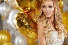 Stående av den blonda unga kvinnan mellan guld- ballonger och bandet Arkivfoton