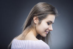 Stående av den blyga och sinnliga unga Caucasian brunettkvinnan med härligt långt hår Posera mot svart Arkivbild