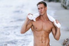 Stående av den brunbrända färdiga manliga modellen med en naken torso på stranden fotografering för bildbyråer