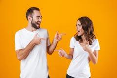 Stående av den caucasian folkmannen och kvinnan i grundläggande bekläda peka fingrar, medan stå tillsammans isolerat över guling arkivbild