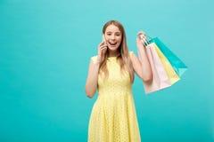 Stående av den caucasian kvinnan för lyckligt mode med shoppingpåsar som kallar på mobiltelefonen Isolerat på blåttbakgrund arkivbilder