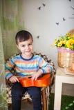 Stående av den caucasian lilla charmiga pojken med en leksakgitarr i selektiv fokus arkivfoto