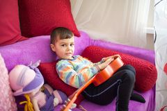 Stående av den caucasian lilla charmiga pojken med en leksakgitarr i selektiv fokus arkivbild