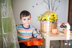 Stående av den caucasian lilla charmiga pojken med en leksakgitarr i selektiv fokus arkivfoton