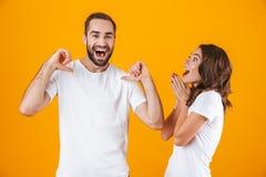 Stående av den caucasian parmannen och kvinnan i grundläggande bekläda peka fingrar, medan stå tillsammans isolerat över guling royaltyfria bilder