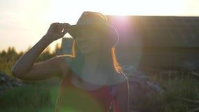 Stående av den caucasian unga nätta kvinnan i cowboyhatt på solnedgången i sommardag lager videofilmer