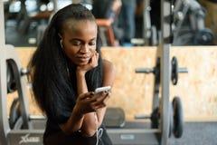 Stående av den charmiga svarta unga kvinnan med lyxigt långt hår som smsar på hennes smartphone i idrottshallen Arkivbild