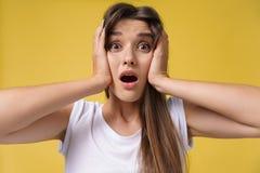 Stående av den chockade förskräckta unga kvinnan i tillfällig vit skjortautfrågningdåliga nyheter med äcklig sinnesrörelse på hen arkivbild