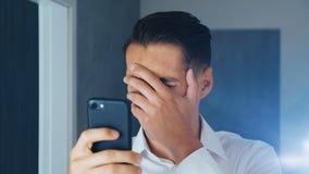 Stående av den chockade och äcklade mannen Den förväxlade mannen såg ett otrevligt meddelande på en smartphone Han oroas omkring stock video