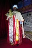 Stående av den coptic ortodoxa kristna prästen med stor vagga-huggen ut kyrklig Biete för kors insida mariam på Lalibela, Etiopie Arkivfoto