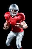 Stående av den defensiva idrottsmannen som rymmer amerikansk fotboll arkivfoton