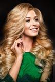 Stående av den eleganta sexiga blonda kvinnan med lång lockigt hår- och glamourmakeup Arkivbild