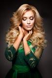 Stående av den eleganta sexiga blonda kvinnan med lång lockigt hår- och glamourmakeup Royaltyfri Foto