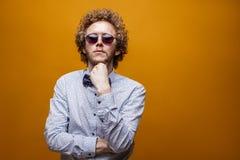 Stående av den eleganta unga mannen i solglasögon på gul bakgrund Arkivbild
