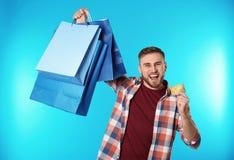 Stående av den emotionella unga mannen med kreditkort- och shoppingpåsar på färgbakgrund arkivbild