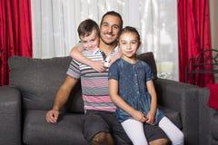 Stående av den enkla pappan med 2 ungar hemma Royaltyfria Bilder