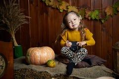 Stående av den förtjusande le flickan som poserar med orange pumpa i nedgångträinre fine arkivbild
