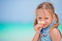 Stående av den förtjusande lilla flickan med blommafrangipanien på strandsommarsemester Royaltyfri Fotografi