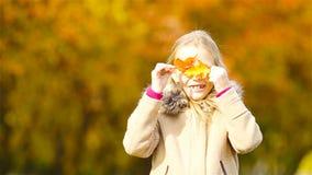 Stående av den förtjusande lilla flickan utomhus på den härliga varma dagen med det gula bladet i nedgång stock video
