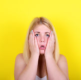 Stående av den förvånade flickan mot gul bakgrund royaltyfri bild