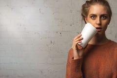 Stående av den förvånade härliga flickan med en kopp kaffe i hand Arkivbild
