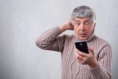 Stående av den förvånade höga mannen som ser med öppna ögon för sned boll in i hans smartphone som är chockad vid vad han ser på  arkivbild