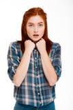 Stående av den förvånade unga härliga ljust rödbrun flickan över vit bakgrund Royaltyfri Fotografi