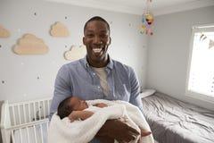Stående av den faderHolding Newborn Baby sonen i barnkammare Royaltyfri Fotografi
