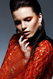Stående av den flott ljusa brunetten i röd skina klänning. Lyx fotografering för bildbyråer