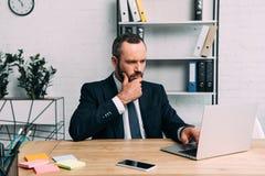 Stående av den fokuserade affärsmannen som arbetar på bärbara datorn på arbetsplatsen arkivfoto