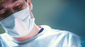 Stående av den fokuserade och koncentrerade kirurgen Performing Surgical Operation i modernt fungeringsrum Kirurgsuturerna arkivfilmer