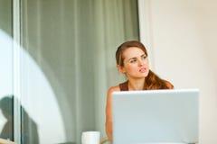 Stående av den fundersama kvinnan som fungerar på bärbar dator Royaltyfri Fotografi