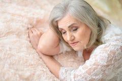 Stående av den fundersamma höga kvinnan som ligger på säng royaltyfri foto
