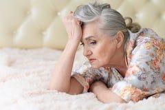 Stående av den fundersamma höga kvinnan som ligger på säng royaltyfria foton