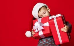 Stående av den fundersamma pojken i jultomtenhatten som isoleras på röd bakgrund arkivfoto