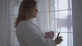 Stående av den fylliga flickan i det vita badrockanseendet nära stort golv-till-tak fönster med koppen kaffe eller te Morgon lager videofilmer