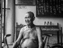 Stående av den gamla asiatiska mannen i traditionellt hus royaltyfria bilder
