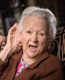 Stående av den gamla kvinnan som sätter handen till hennes öra royaltyfria foton